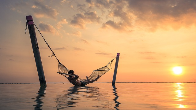 Sunset and person lying in a hammock over the sea